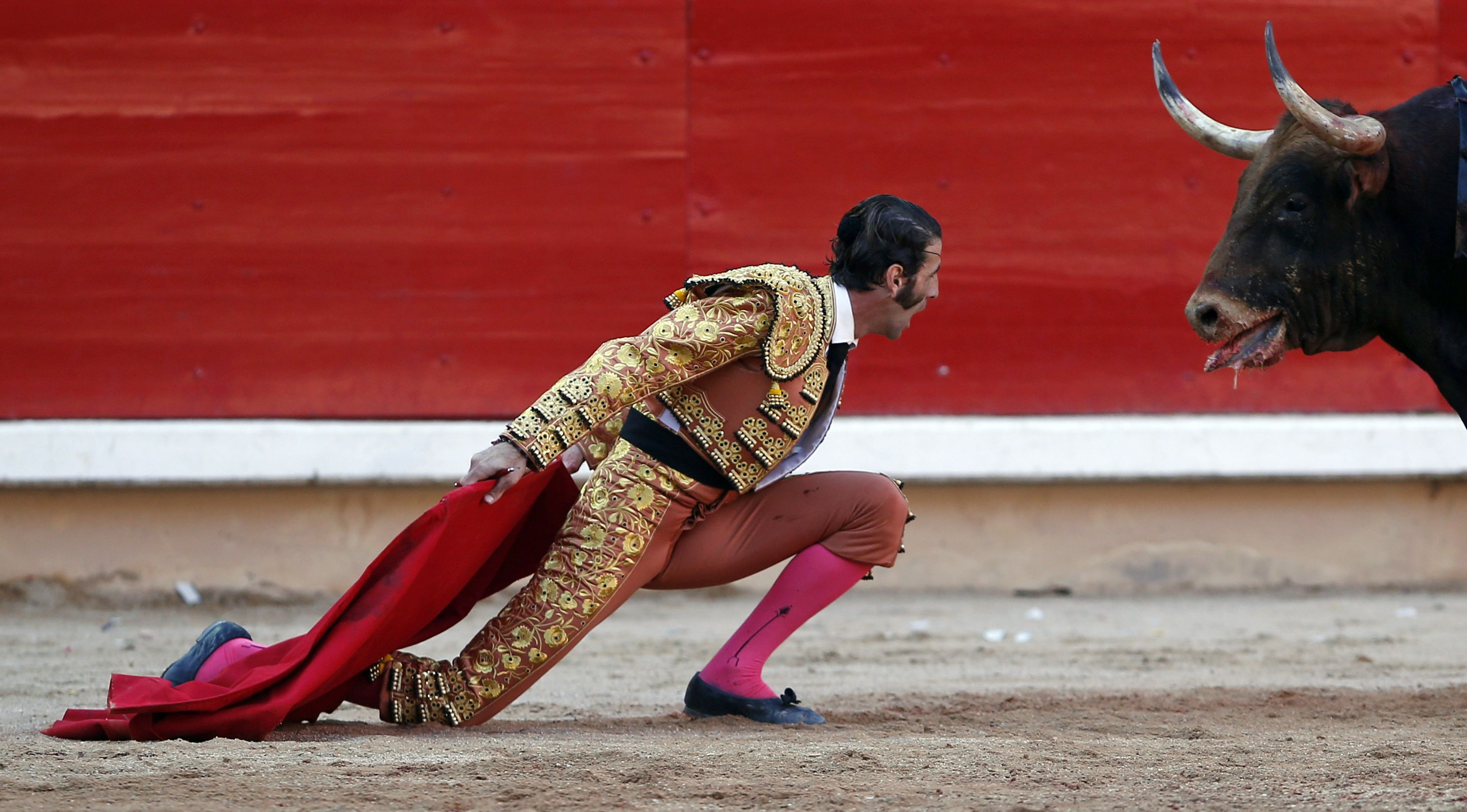 Spanish bullfighter Juan Jose Padilla kneels down in front of a bull during the last bullfight of the San Fermin festival in Pamplona July 14, 2012. Padilla lost an eye after getting gored last October during a bullfight in Zaragoza, northern Spain. He made a comeback five months afterwards.   REUTERS/Susana Vera (SPAIN - Tags: SOCIETY TPX IMAGES OF THE DAY)