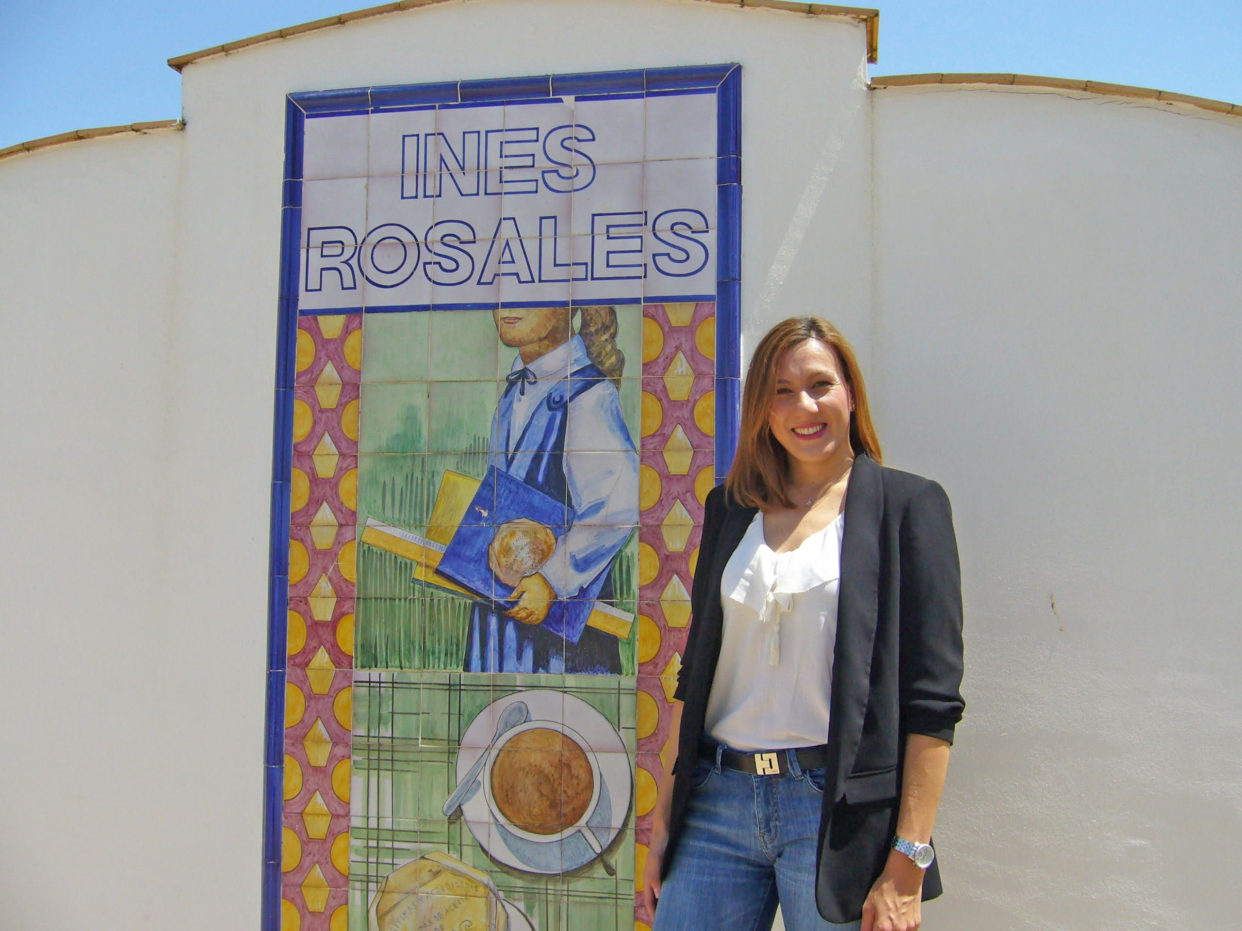 Valle Guerrero posando junto al azulejo de la fábrica de Inés Rosales en Sevilla