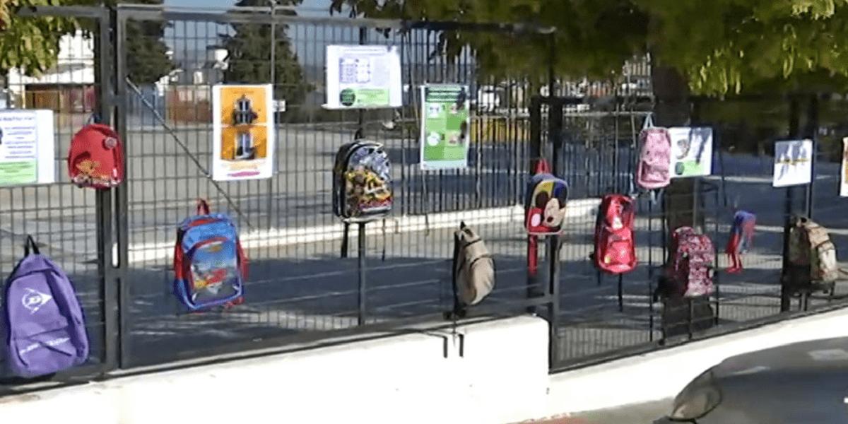 Padres cuelgan mochilas en un colegio en señal de protesta